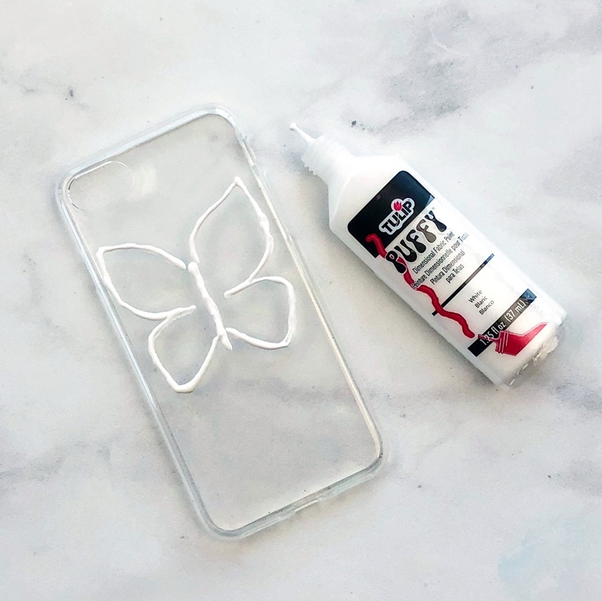 Outline butterfly in White Dimensional Fabric Paint on clear case