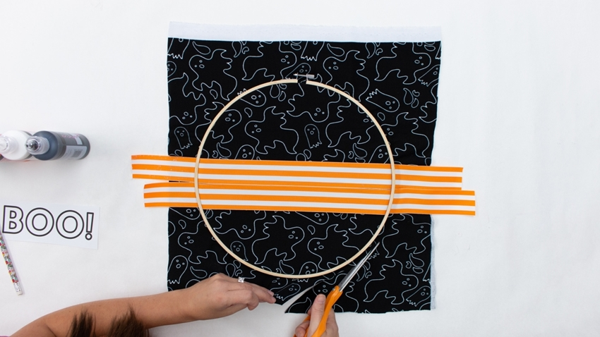 Glue ribbon to fabric and secure between hoops