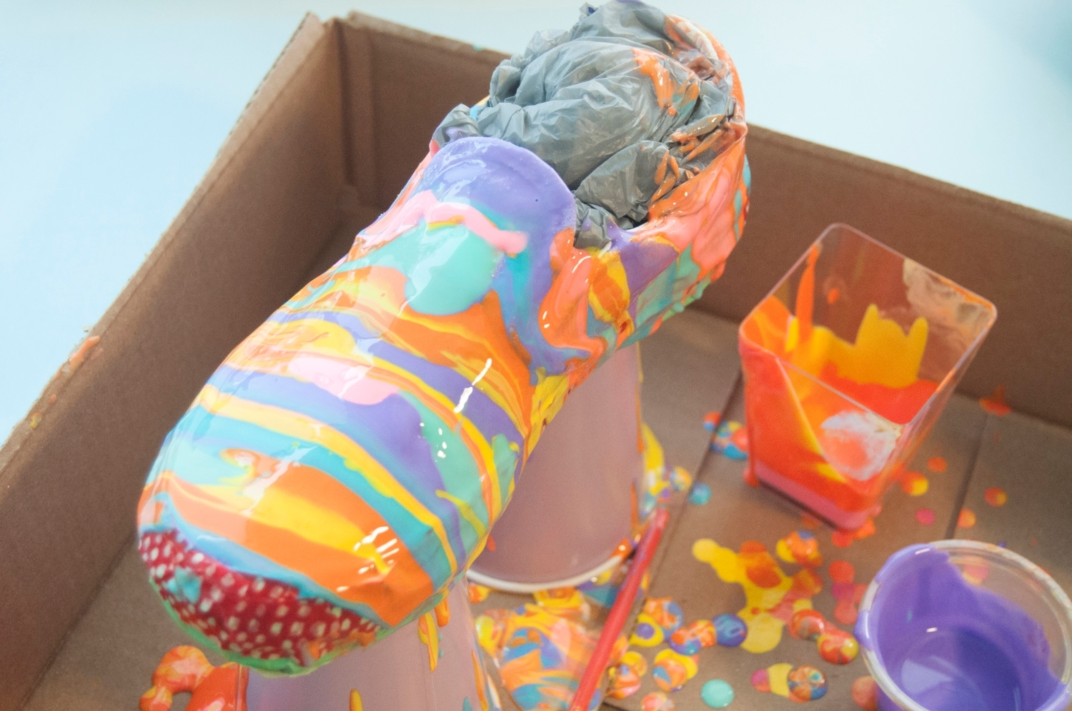 Keep alternating pouring paints until shoes are covered