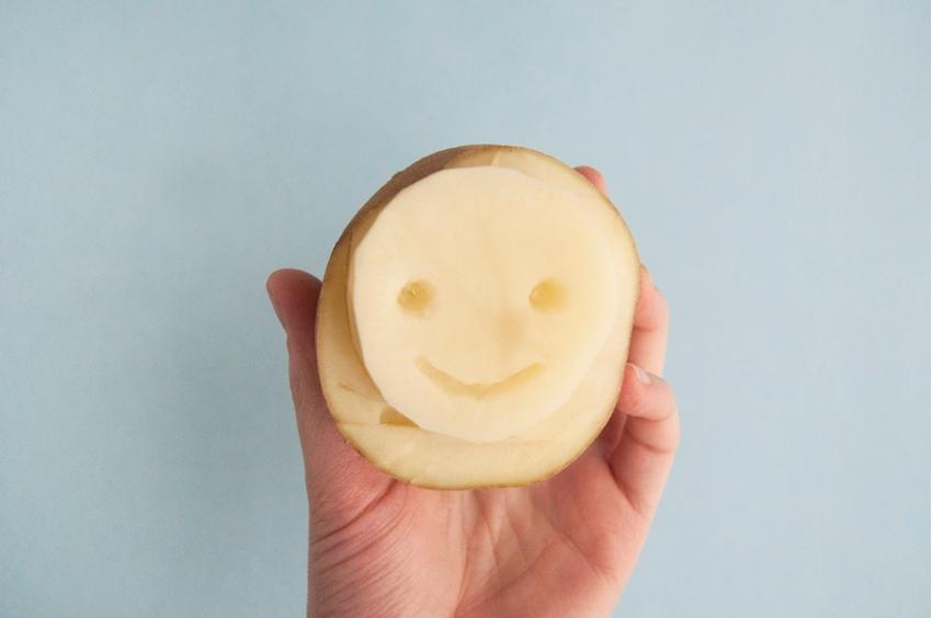 Carve smiley face into potato