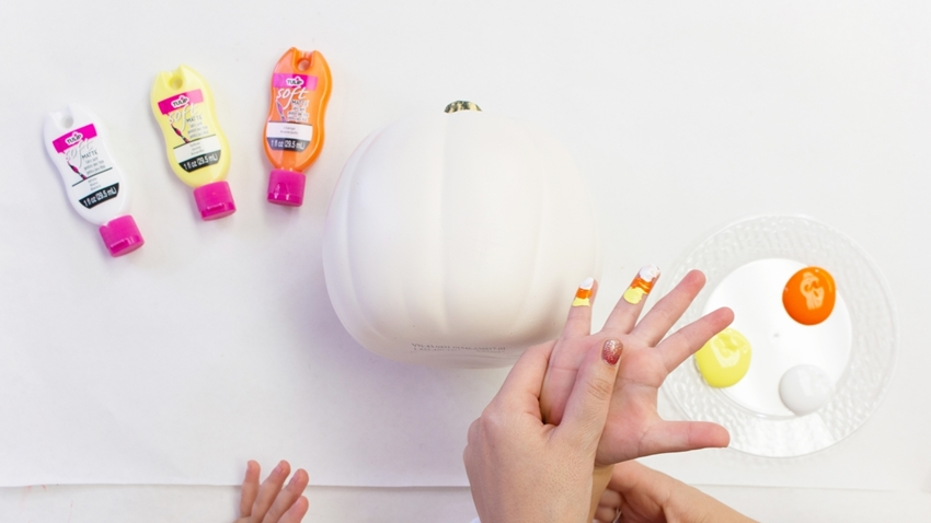 Paint stripes onto child's finger in candy corn color order