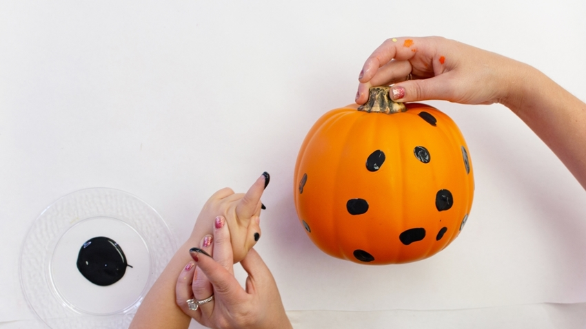 Dip finger in black paint and press onto pumpkin