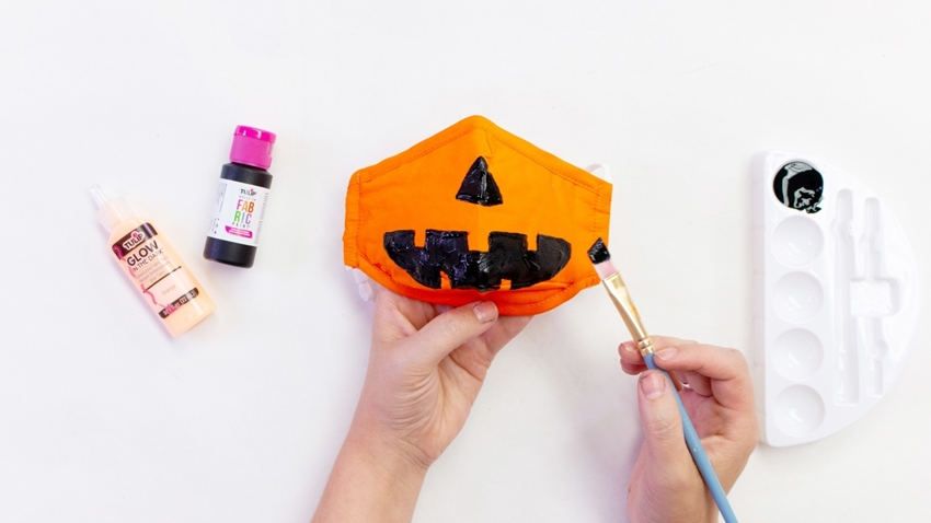 Use fabric paint to decorate your pumpkin mask