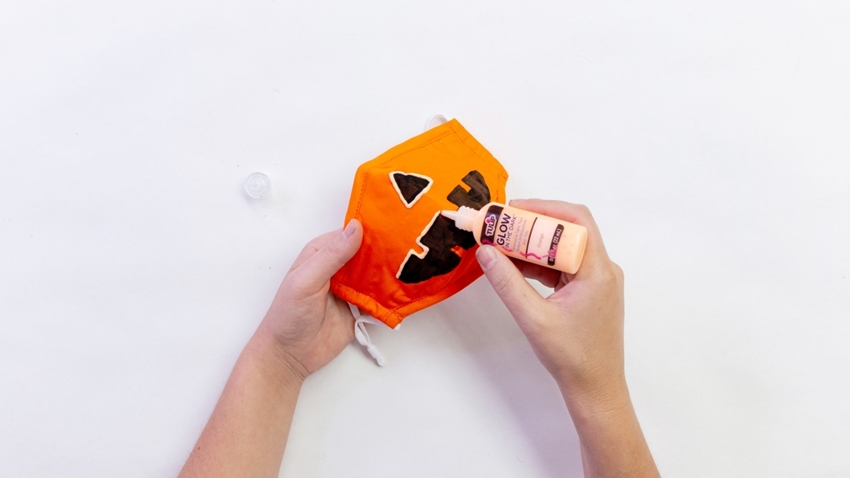 Outline the jack-o-lantern face with Glow in the Dark Dimensional Fabric Paint